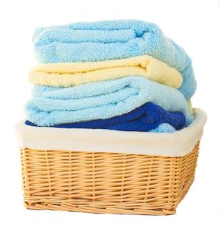 Mucchio della merce nel cestino lavata dell'asciugamano isolata