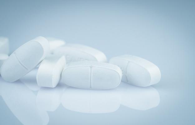 Mucchio delle pillole oblunghe bianche delle compresse sul fondo di pendenza. pillole bianche della compressa antibiotica. industria farmaceutica. prodotto della farmacia. droga in farmacia farmacia o ospedale. resistenza ai farmaci antibiotici.