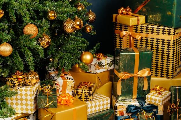 Pila di regali verdi e oro avvolti per natale