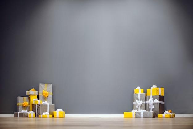 Mucchio di regali di natale gialli e grigi