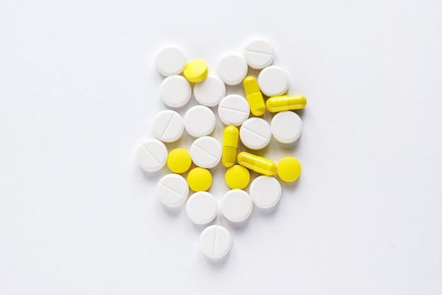 Pila di compresse gialle e bianche sulla superficie bianca.
