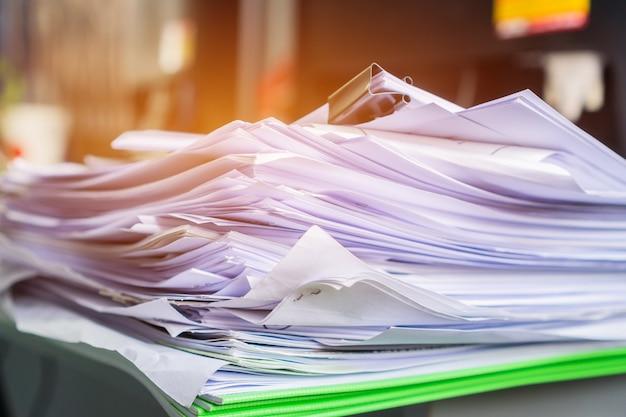 Cartelle di documenti accatastate ad alto riciclo, impilare carta da lavoro sulla scrivania disordinata o scartoffie in ufficio. il vecchio documento raggiunge i moduli dei documenti della cartella di stampa, usa il riciclaggio per risparmiare
