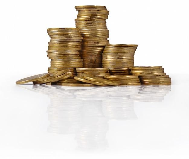 Mucchi di monete d'oro su sfondo bianco