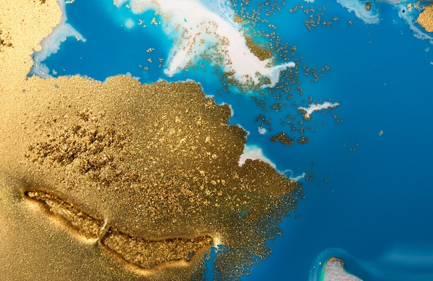 Mucchi di paillettes dorate su macchie blu di vernice. vernice di versamento astratta