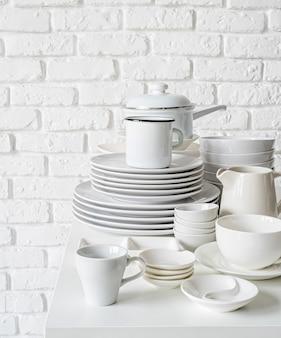Mucchi dei piatti e delle stoviglie ceramici bianchi sulla tavola sul muro di mattoni bianco