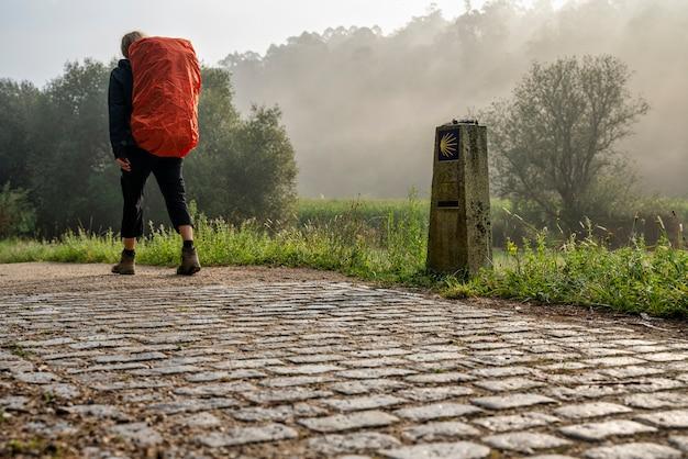 Pellegrino che cammina sulla strada per san giacomo (santiago) in una giornata nebbiosa in galizia