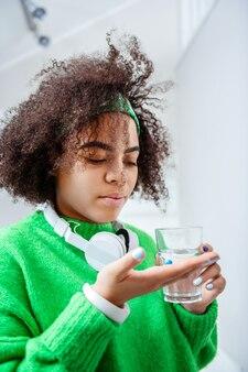 Pillola nel palmo. bella ragazza afroamericana prendendo pillole di vitamina e bevendolo con acqua pulita