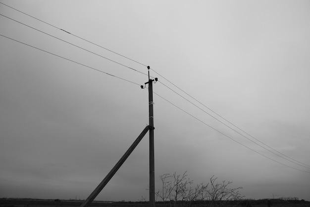 Pilastro con fili elettrici nella nebbia scura, paesaggio cupo
