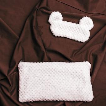Cuscino e maschera per gli occhi per dormire dalla pelliccia con orecchie divertenti sul letto