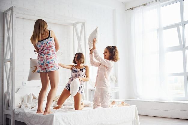 Battaglia di cuscini. felici amiche che si divertono al pigiama party in camera da letto.