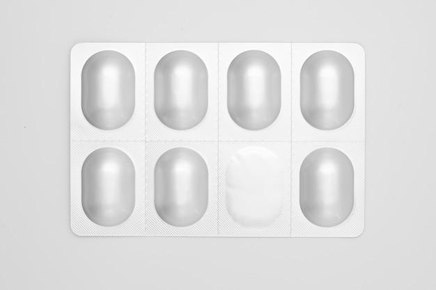Pillole in blister di alluminio isolato su bianco.