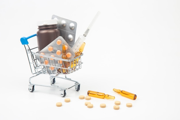 Pillole, fiale e siringhe per iniezione in un paniere di mercato su uno sfondo bianco. affari e medicina