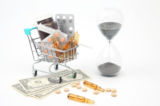 Pillole, fiale e siringhe per iniezione, dollari di denaro e clessidra su una superficie bianca. affari e medicina.