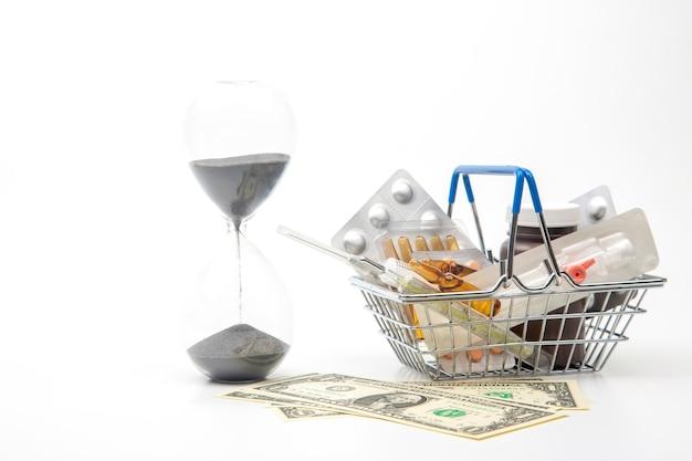 Pillole, fiale e siringhe per iniezione, denaro e clessidra su uno sfondo bianco. affari e medicina.