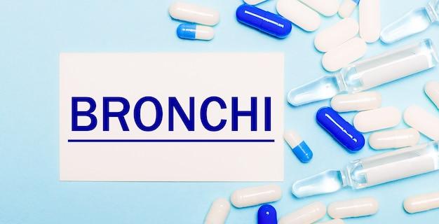 Pillole, fiale e un cartoncino bianco con la scritta bronchi su sfondo azzurro. concetto medico