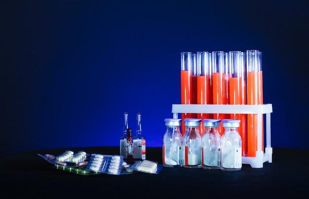 Pillole su uno sfondo di provette con liquido rosso e fiale su sfondo nero