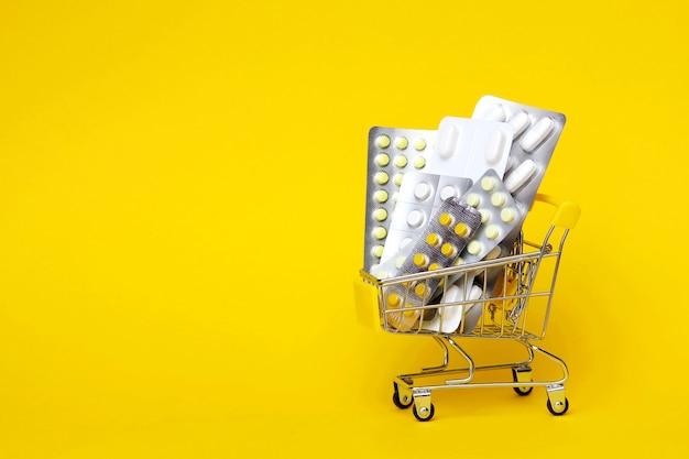 Pillole in blister in un carrello della spesa giocattolo