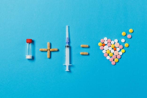 Il flacone di pillole più l'ago della siringa vuoto equivale a compresse rotonde colorate di farmaci a forma di cuore isolato su sfondo blu