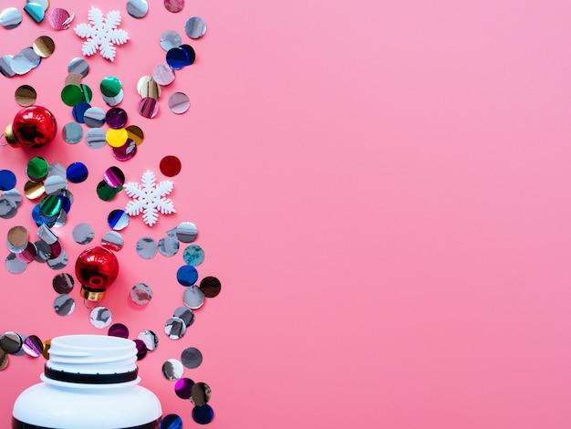 Pillole, coriandoli, giocattoli di natale su uno sfondo rosa