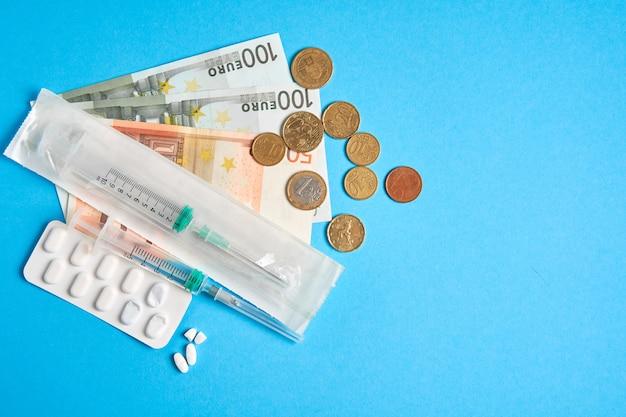 Le pillole svuotano le bolle per la siringa individuale dei soldi e la bugia dei soldi su un fondo blu