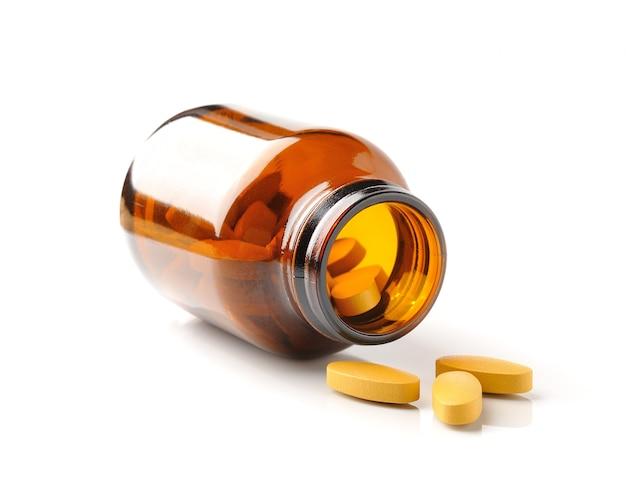 Pillole dalla bottiglia sul bianco