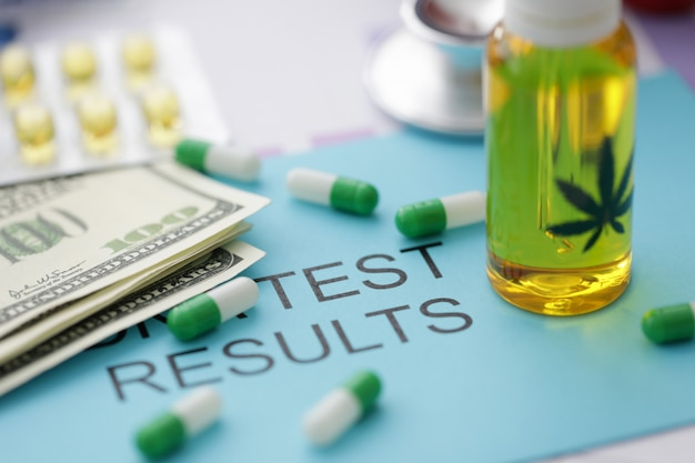 Barattolo di pillole di olio di marijuana sulla busta blu con risultato del test di iscrizione.