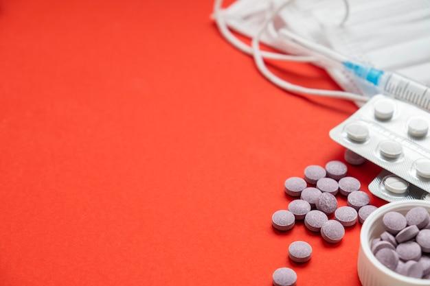 Pillole e maschere protettive della medicina su fondo rosso. medicinali. copia spazio