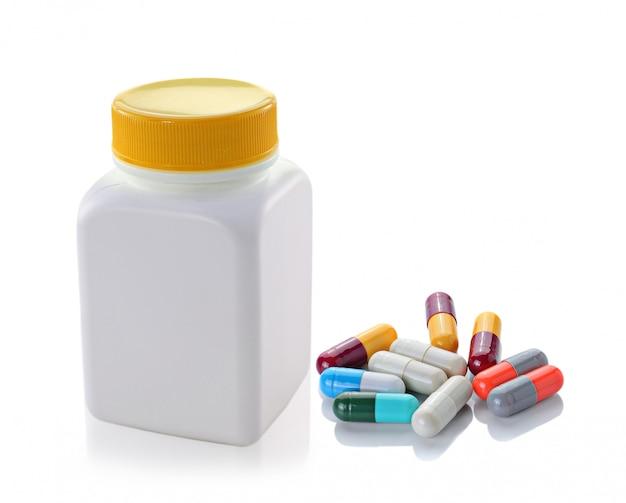 Pillole dalla bottiglia su bianco isolato