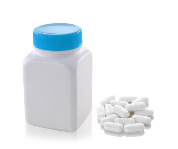 Pillole dalla bottiglia su spazio bianco