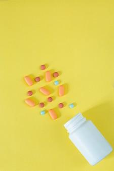 Pillole e flaconi di pillole su sfondo giallo