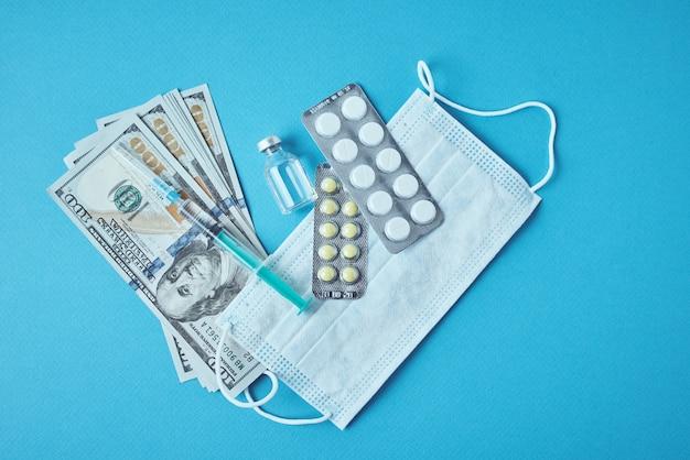 Pillole, maschera protettiva e banconote in dollari sul blu