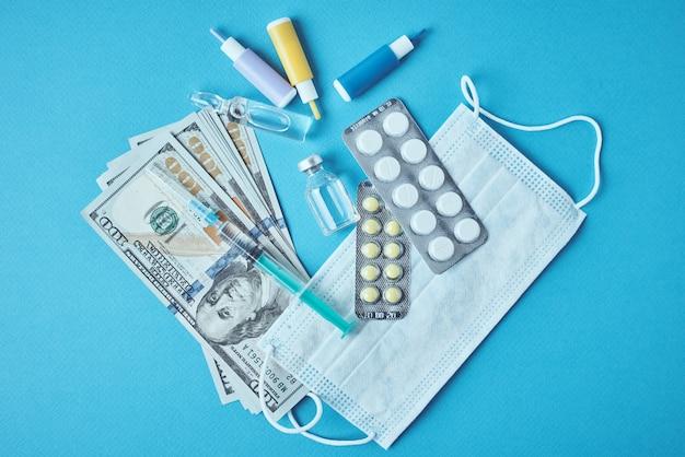 Pillole, maschera protettiva, articoli medici e banconote da un dollaro sul blu