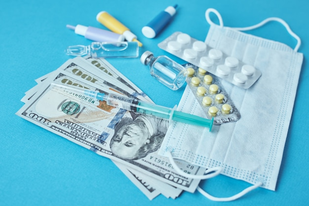 Pillole, maschera protettiva, oggetti medici e banconote da un dollaro. concetto costoso della medicina. industria farmaceutica e assicurazione medica