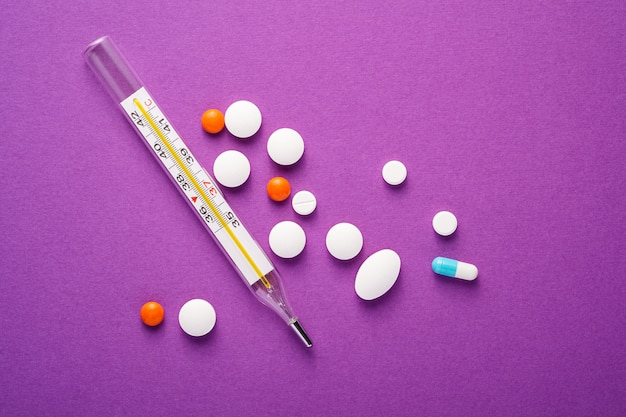 Pillole, compresse e termometro analogico sulla superficie viola viola, concetto medico sanitario, antibiotici e cura, spazio copia vista dall'alto