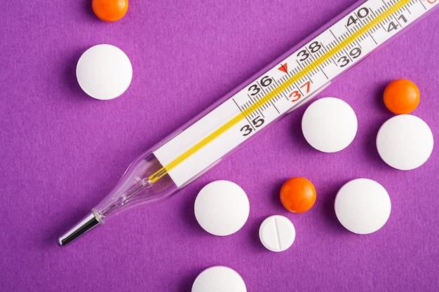 Pillole, compresse e termometro analogico sulla superficie viola viola