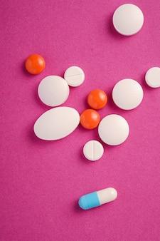 Pillole e compresse su sfondo viola rosa brillante, concetto medico sanitario, antibiotici e cura, vista dall'alto
