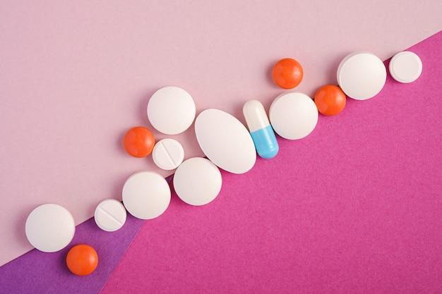 Pillole e compresse in fila diagonale su sfondo rosa, viola e viola brillante, concetto medico sanitario, antibiotici e cura, vista dall'alto