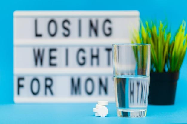 Pillole per la perdita di peso su una superficie blu con un bicchiere d'acqua