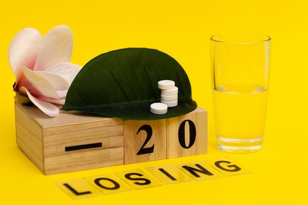 Pillole per perdita di peso su una foglia su blocchi di legno