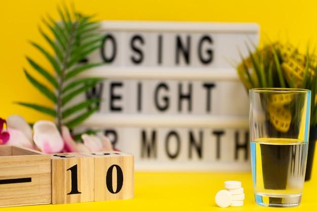 Pillole per la perdita di peso su una superficie gialla con blocchi di legno
