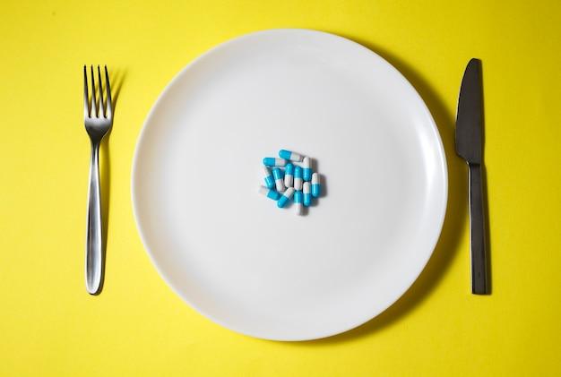 Pillole su un piatto bianco con coltello e forchetta su sfondo giallo