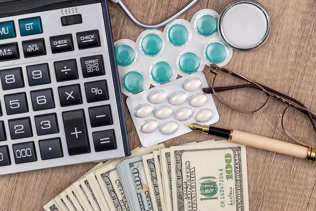 Pillole con calcolatrice e soldi sulla scrivania in legno
