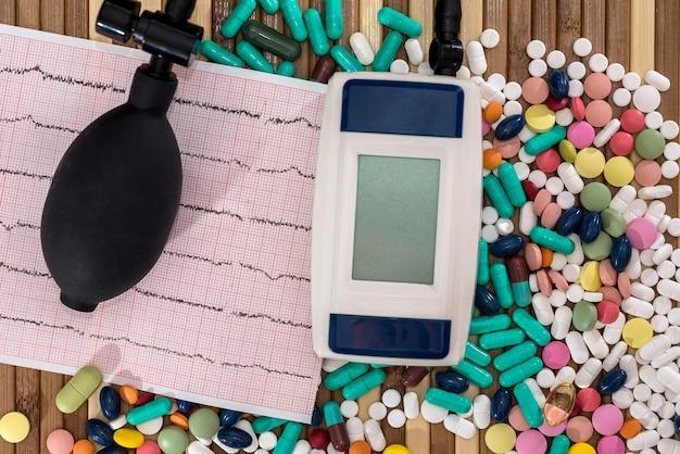 Pillole con cardiogramma e tonometro su tavola di legno