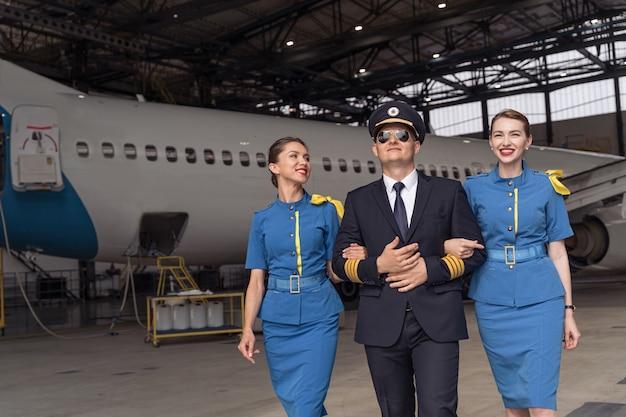 Pilota e assistenti di volo camminano insieme nell'hangar