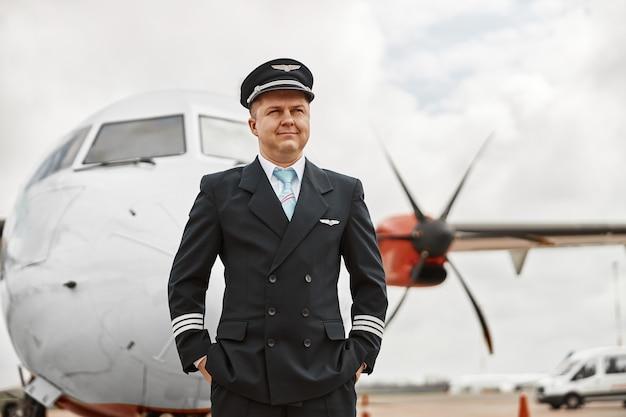 Pilota in piedi sulla pista su sfondo jet aereo. aereo passeggeri moderno. l'uomo europeo sicuro con le mani in tasca indossa l'uniforme. aviazione civile commerciale. concetto di viaggio aereo