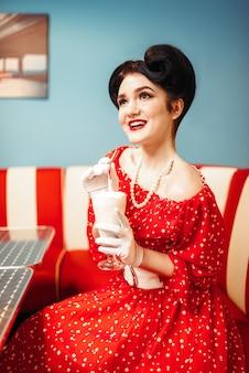 Pin up girl beve milkshake con una cannuccia