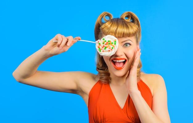 Pin sulla ragazza con lecca-lecca sul bastone isolato su sfondo blu dolcezza donna sorridente con colorato