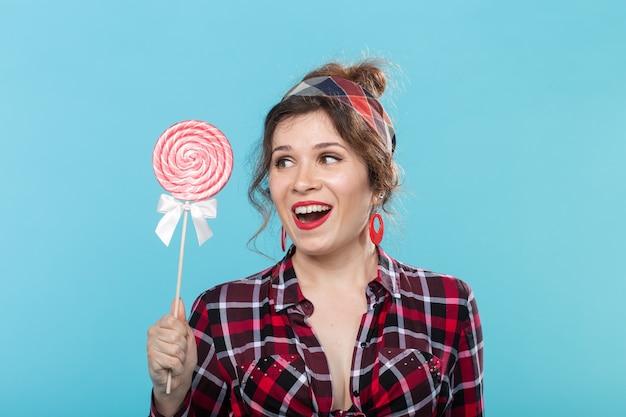 Concetto di donna, moda e persone pin-up - ritratto di donna pin-up con lecca-lecca sul blu