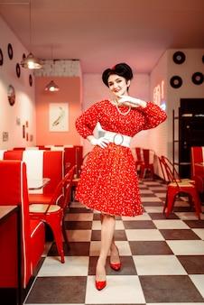 Pin up donna in abito rosso con puntini bianchi, stile vintage. interiore del caffè retrò con pavimento a scacchiera