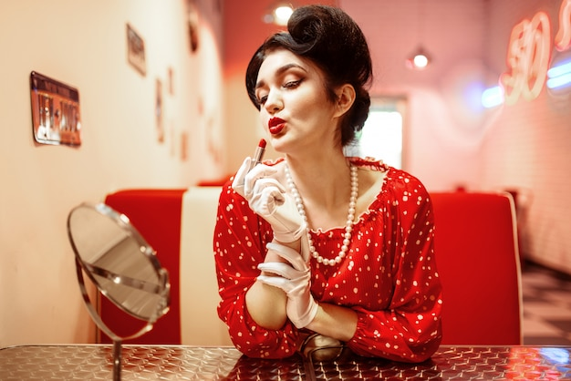 Pin up donna con rossetto luminoso in mano seduto contro lo specchio, vestito con pois, stile vintage. moda americana retrò cafe 50